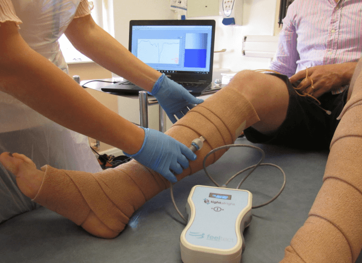 A patient with their legs bandaged up sits on a hospital bed, while a medical professional uses FeelTect's Tight Alright device on them.