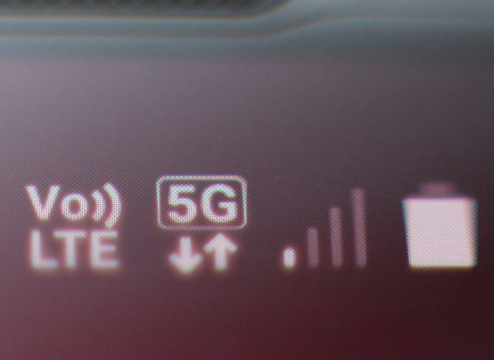 Extreme close-up of a smartphone status bar displaying the symbol for 5G data next to the battery and signal icons.
