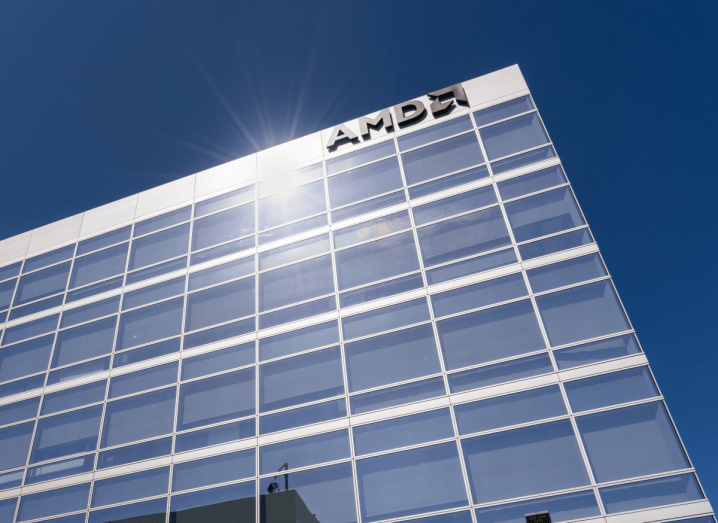 The sun reflecting off a glass building that has the AMD logo on it.