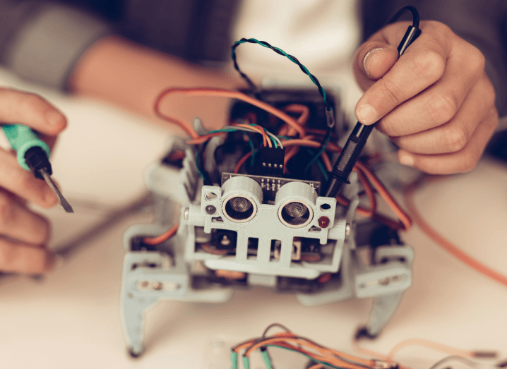 A child's hands building a small robot and holding tools.