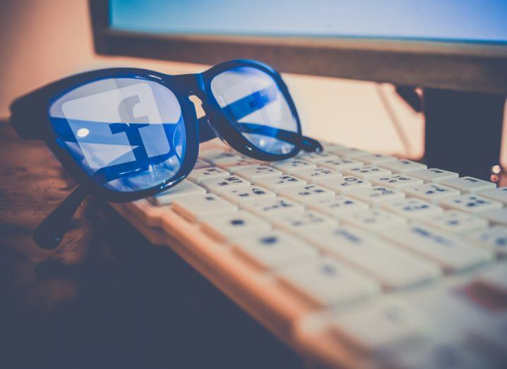 Facebook logo reflection on a pair of thick-rimmed glasses.