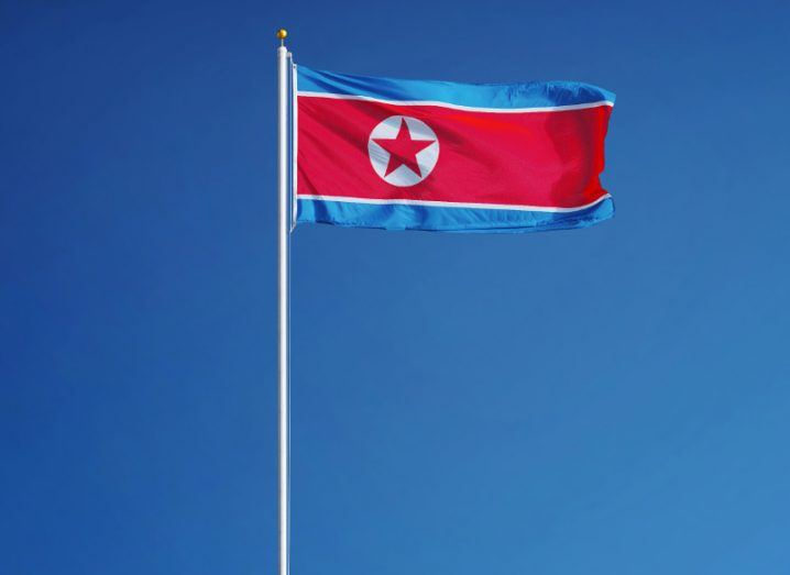 Blue and red north Korean flag billowing in the wind against a cloudless sky in day time.