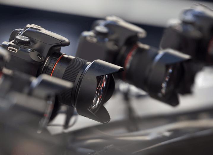 Three DSLR cameras on small tripods.
