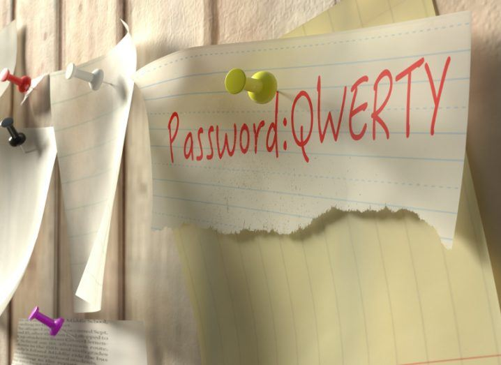 Note with password 'qwerty' on a wooden kitchen wall with pins.