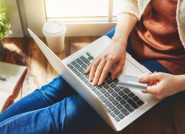 View from above of person using their laptop while holding a payments card in one hand, online shopping.