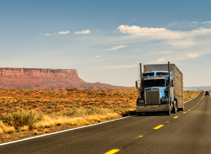 A truck driving down a long road in an Arizona desert, underneath a slightly cloudy sky.