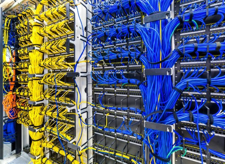 A large server rack with numerous blue and yellow ethernet cables streaming out of it.