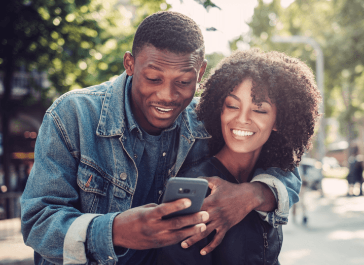 A man wearing a denim jacket has his arm around a woman in a black jumper. They are on a public street, laughing together as they both look at his mobile phone.