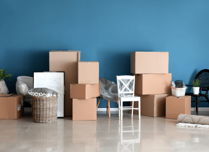 Unpacked boxes and items of furniture in a room in front of a blue wall, where someone has just moved in.