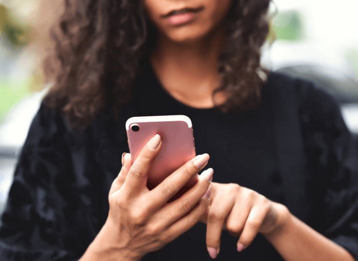 A woman in a black jumper with brown curly hair holds an iPhone.
