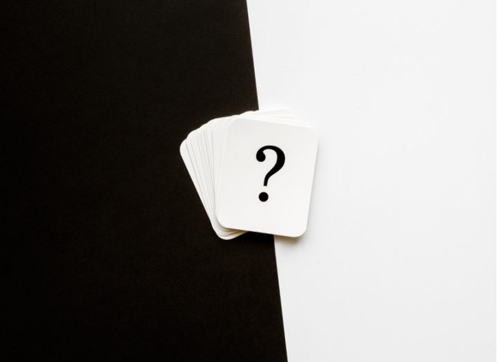 A stack of white cards bearing large black question marks fanned out on a background that is half white, half black.