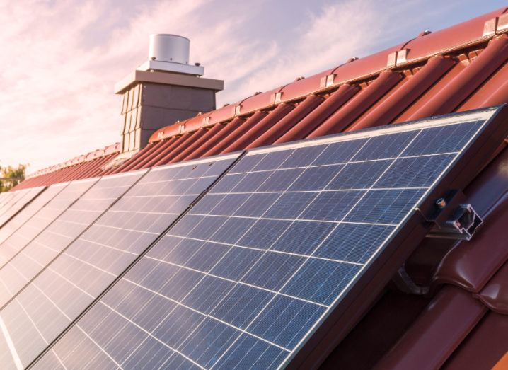 View of solar panels affixed to the roof of a residential property drenched in the light of a sunrise.