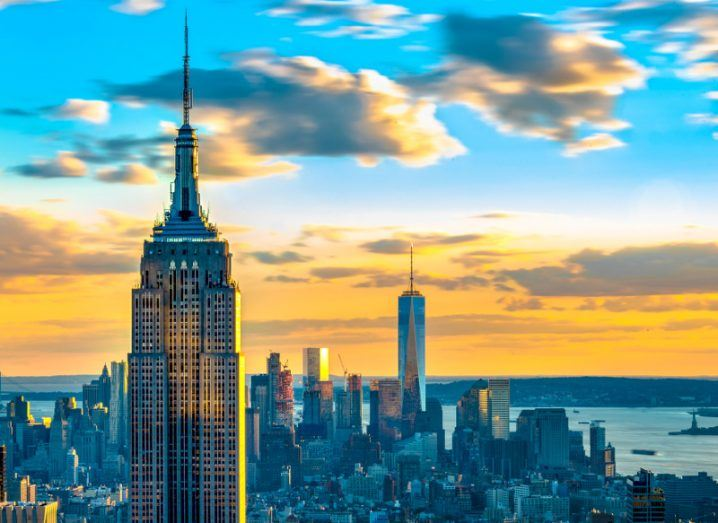 High-rise view of the New York City skyline at sunrise, including the Empire State Building and One World Trade Center.