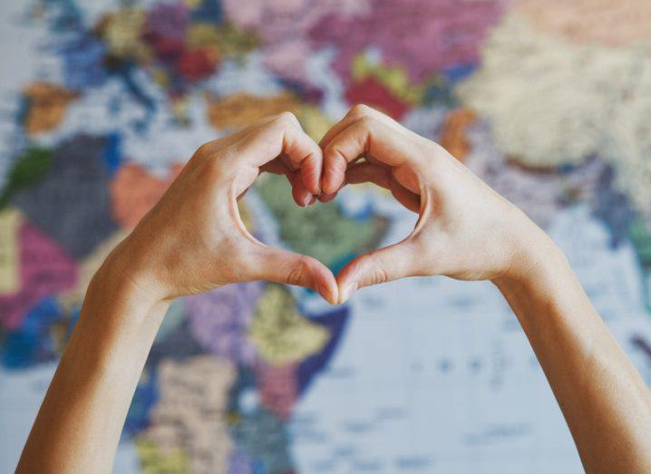 A woman's hands form the shape of a heart over a colourful world map in the background.