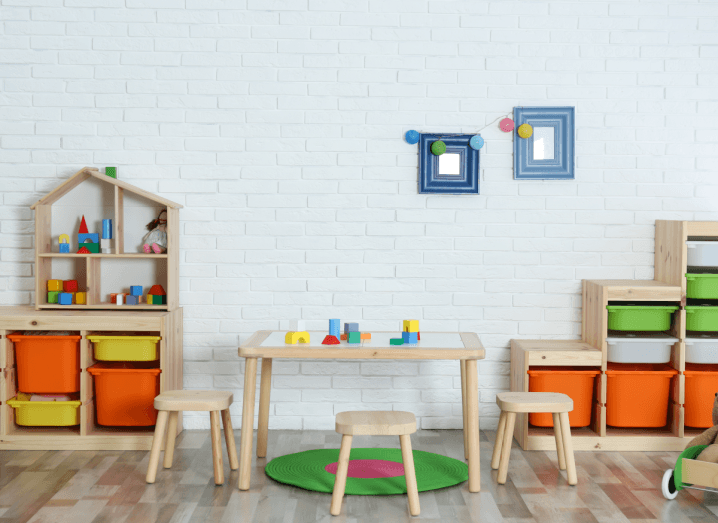 A child's playroom, with colourful drawers, stools and toys.