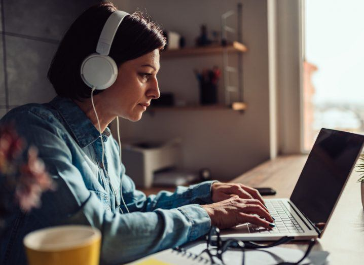 Woman in denim shirt using laptop and listening to music with headphones.