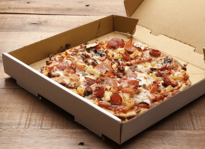 A pizza with ham, pepperoni, pineapple and chicken in a brown takeaway box on a wooden table.