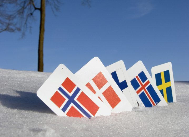 Cards bearing the flags of Sweden, Denmark, Finland, Norway and Iceland sticking upright in the snow with a bare tree in the background.