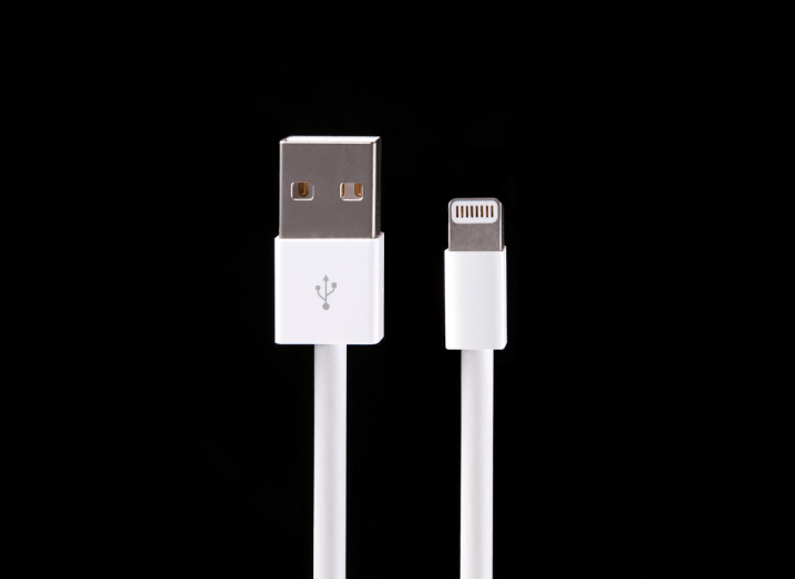 An iPhone Lightning cable in front of a black background.