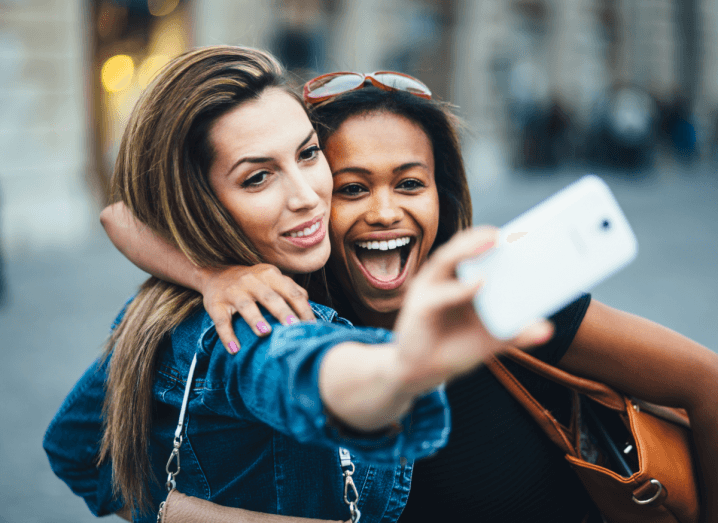 A woman in a denim jacket with dark hair holds her phone in the air to take a selfie with her friend in a black T-shirt, who is holding an orange handbag.