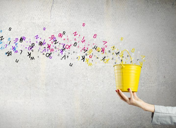 An outreached hand holds a yellow bucket from which a plum of colourful letters are streaming.