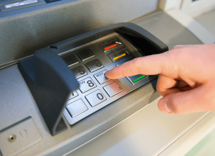 A hand typing a PIN into the keypad of an ATM.