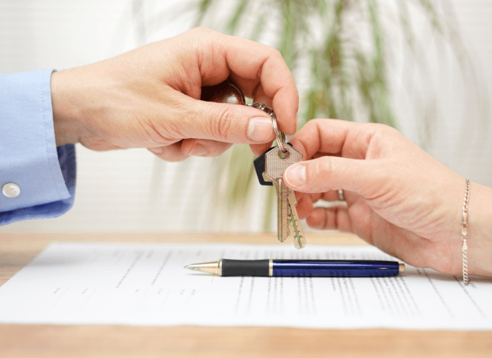 A landlord exchanging keys to a tenant over a contract and pen.