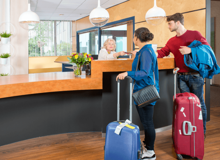 A woman in a blue shirt and black skinny jeans, checks into a hotel with a man wearing a red jumper and blue jeans. They both have luggage with them.