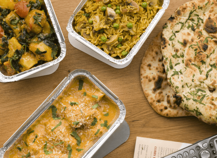Foil trays of chicken korma, sag aloo, mushroom pilau and naan bread on a wooden table.
