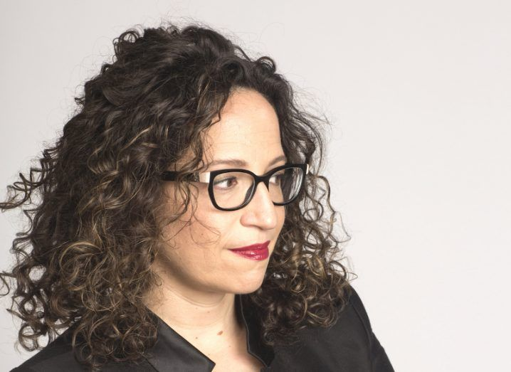 Head shot of woman with glasses and tightly curled hair.