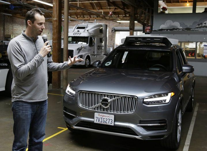 Anthony Levandowski holding a microphone beside a Volvo car containing self-driving technology.