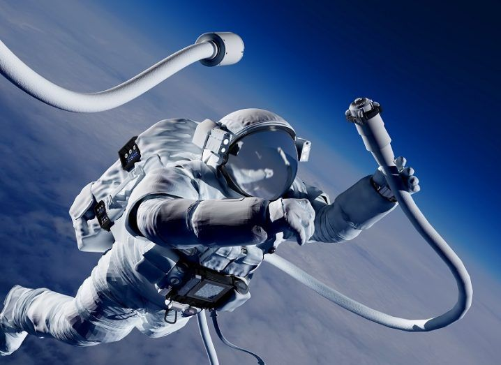 Illustration of astronaut in orbit connecting two cables together.