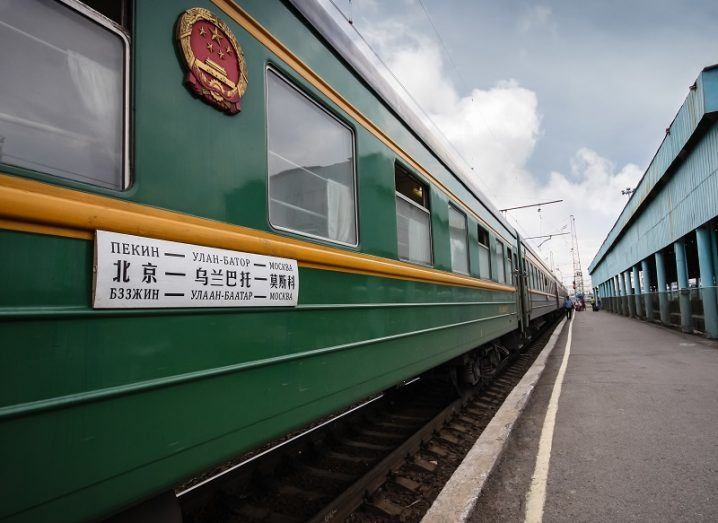 A green Trans-Siberian railway train carriage waiting at a station.