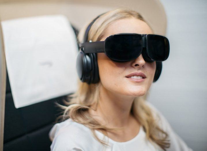 Woman wearing VR headset on an aircraft passenger seat.