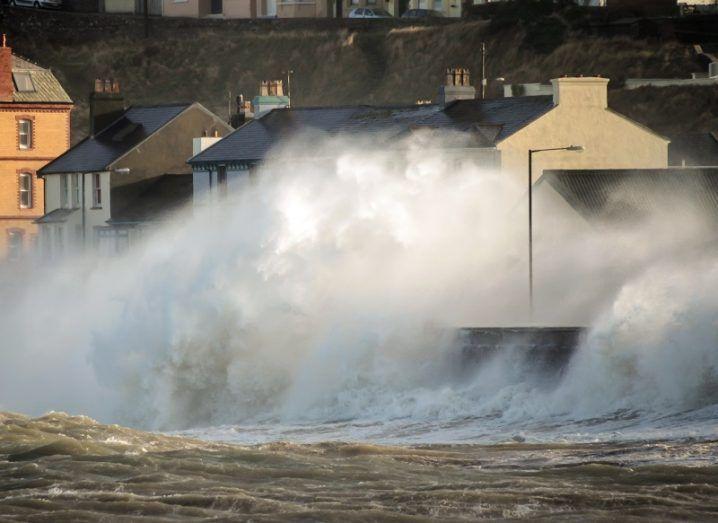 Huge wave crashing over a coastal wall of a seaside town.