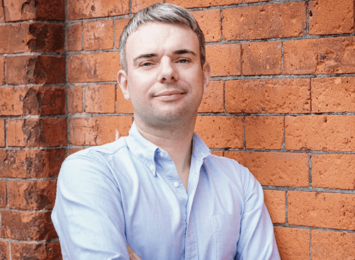 Colm O'Carroll, the new CFO of SoapBox Labs, stands in front of a red brick wall with his arms crossed. He is wearing a blue shirt.