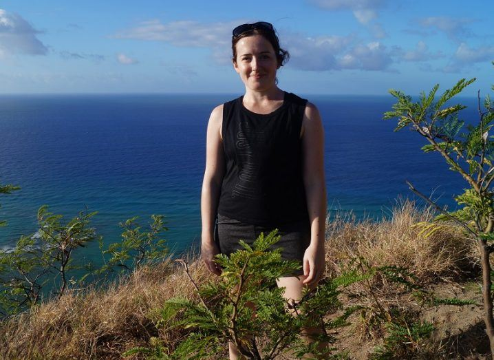 Jasmine Headlam smiling in a black tank top standing on a grassy cliff with a blue ocean in the background.