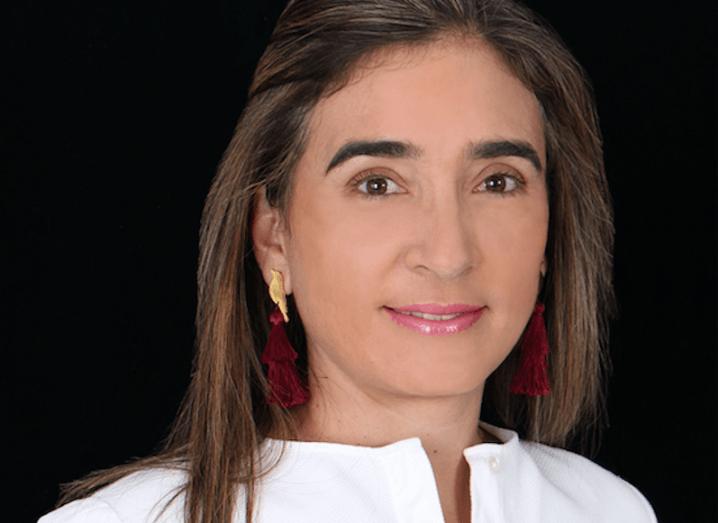 Head shot of Kushki co-founder Daniela Espinosa, a woman with long dark hair wearing a white shirt and red, dangling earrings.