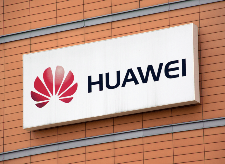 Huawei's red logo printed beside the company's name on a white background, on a billboard on a red brick wall.