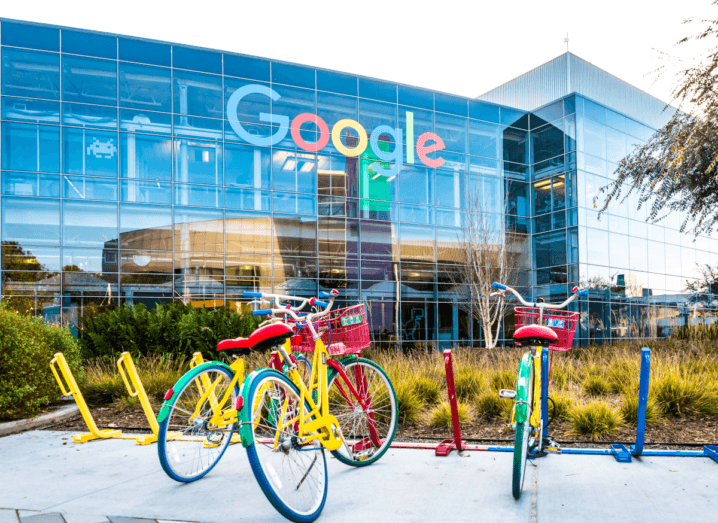 Colourful bikes parked outside of a large Google office building.