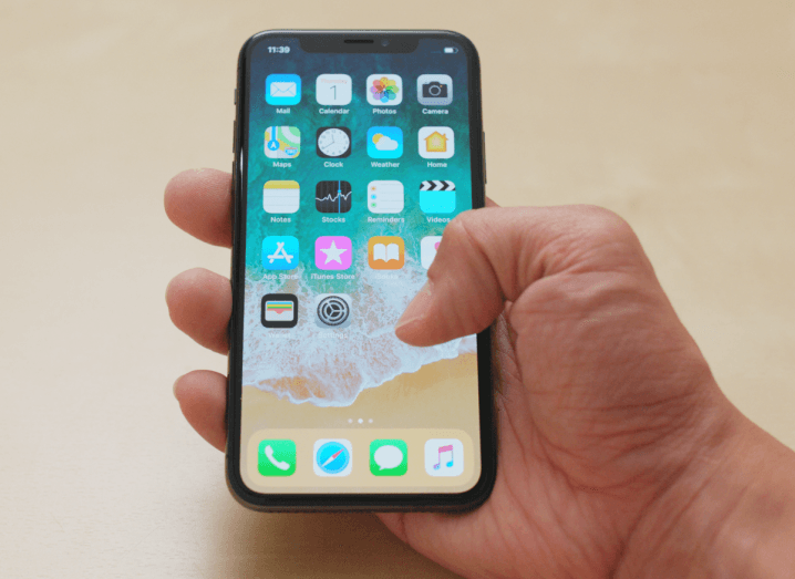 A hand holding an iPhone X.