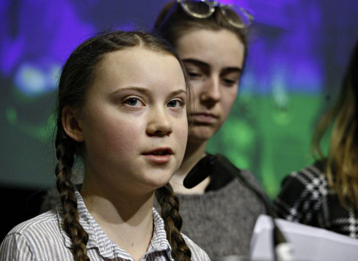 Greta Thunberg, a young girl with her hair in pigtails, speaks at a podium with another young woman standing behind her.