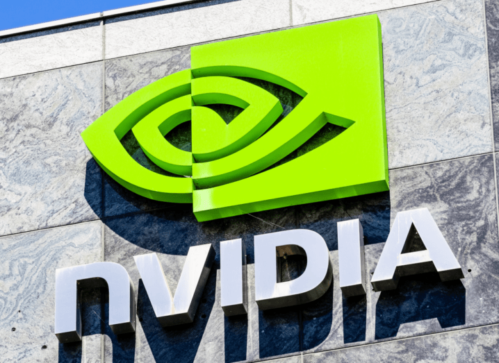 The NVIDIA logo and symbol displayed on a grey wall of the company's Silicon Valley campus, in front of a blue sky.