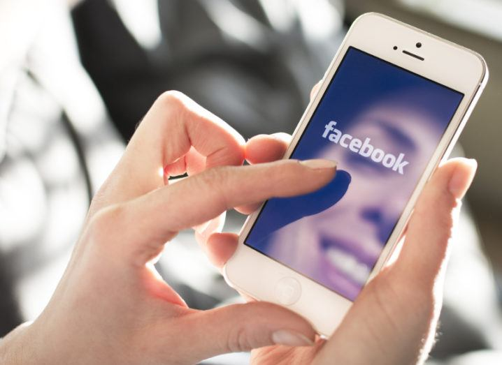 View of Facebook app open on white smartphone.