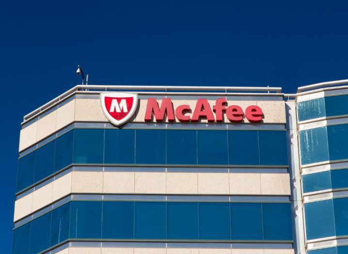 View of glass front modern façade of McAfee corporate headquarters on a bright day against a cloudless turquoise sky.