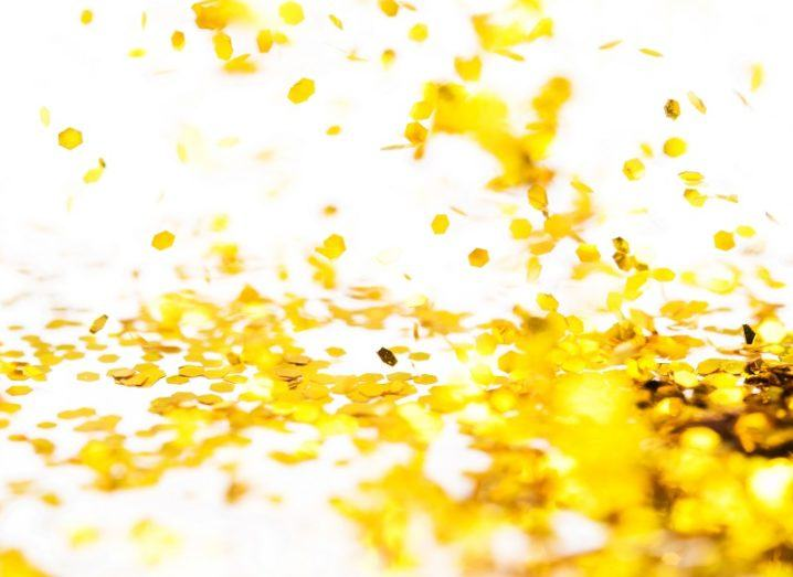 Gold glitter falling to the ground against a white background.