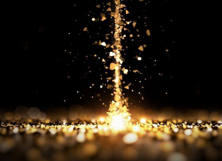 3D render of a stream of gold particles projecting upwards.