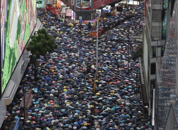 Aerial shot of thousands of protesters with umbrellas marching through streets of Hong Kong.