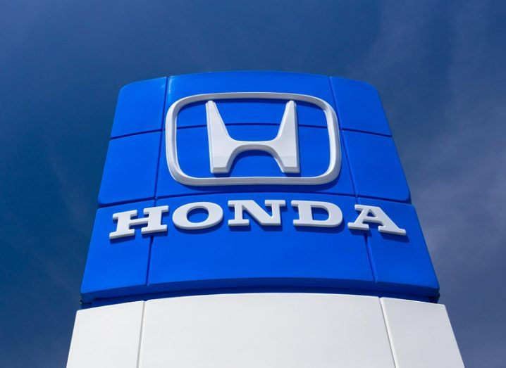Blue sign with the Honda badge and name on it against a dark blue sky background.