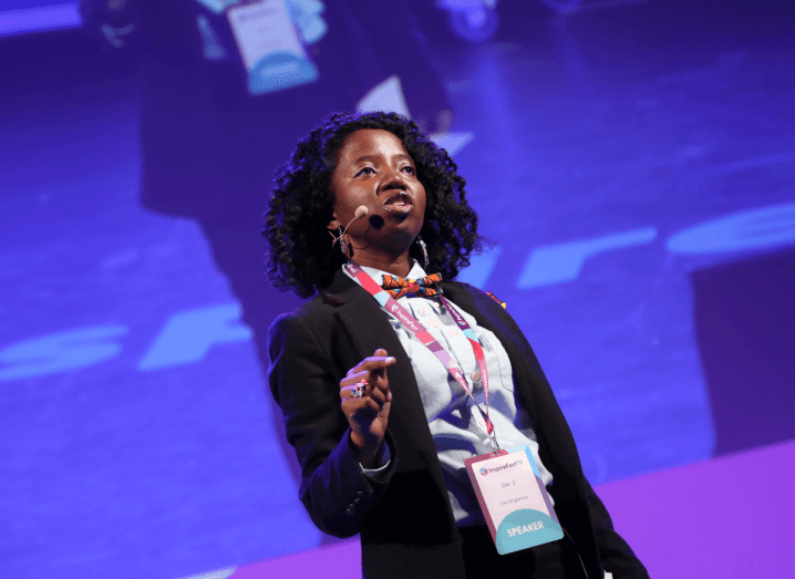 Zile, a dark-haired woman, stands on stage wearing a black suit, white shirt and a colourful bowtie. She is also wearing an Inspirefest speaker's pass.